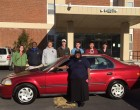 Equashia Mumeen poses with her new Honda Civic . She's joined by  Community Empowerment Fund Program Coordinator Maggie West (far left), Crown Honda Sales Consultant Walter Sturdivant  (second from left) and students from the Kenan-Flagler Business School.