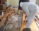Workers tear up ruined floorboards.