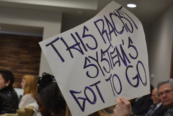 Protester sign at UNC Board of Governors meeting. Photo via Blake Hodge.