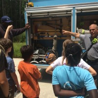 Two firemen from the Chapel Hill Fire Department explain the different tools on the fire truck. Photo via Erin Wygant.