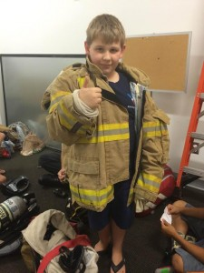 Gill Corbett was the first to try on a fireman's coat. Photo via Erin Wygant.